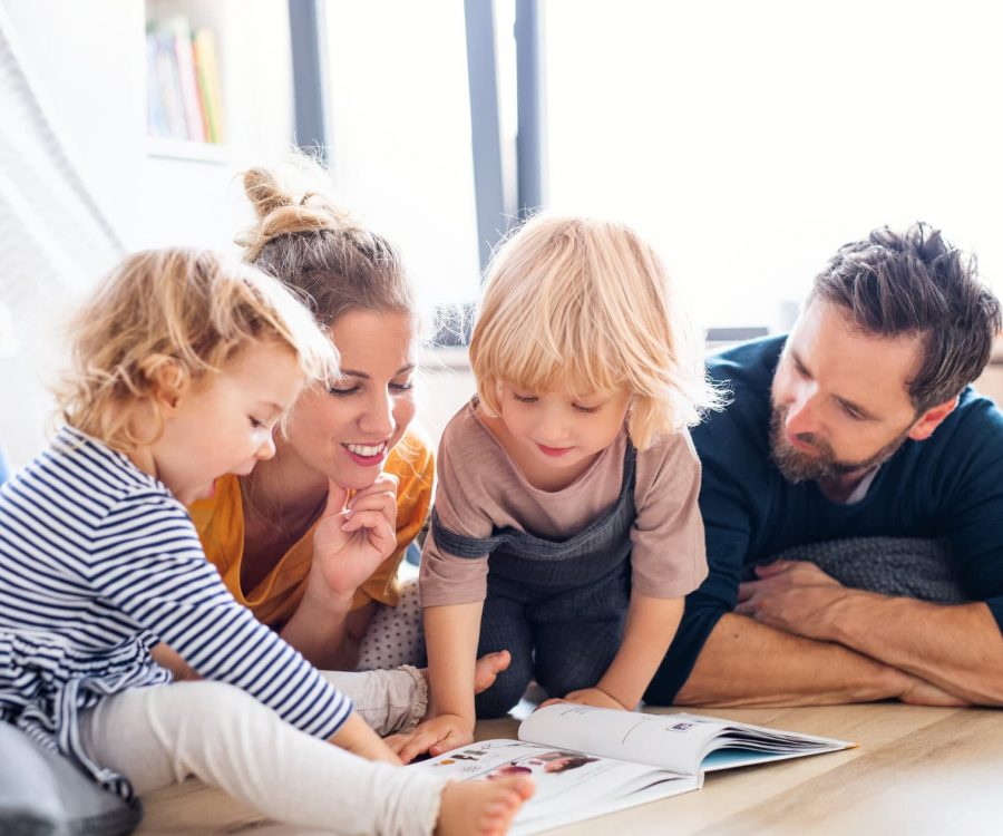Front view of young family with two small children indoors in bedroom reading a book.
